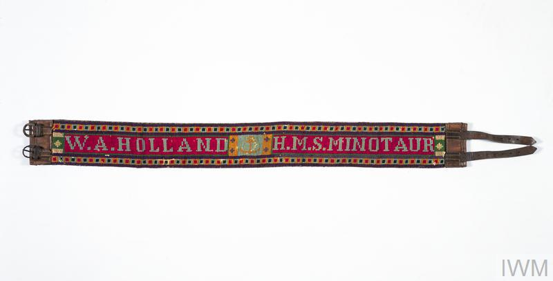 This tapestry belt is an example of needlework created by a serviceman; This tapestry belt is an example of needlework created by a serviceman. It has been decorated with tapestry work to spell out the name of its maker, W A Holland, and the ship in which he served, HMS Minotaur. HMS Minotaur was an armoured cruiser in which Holland served after his previous ship, HMS Warrior (also an armoured cruiser), was sunk on 1 June 1916 at the Battle of Jutland
