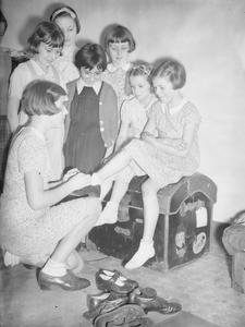 CHANNEL ISLAND EVACUEES TRY ON AMERICAN CLOTHING IN MARPLE, CHESHIRE, ENGLAND, 1940