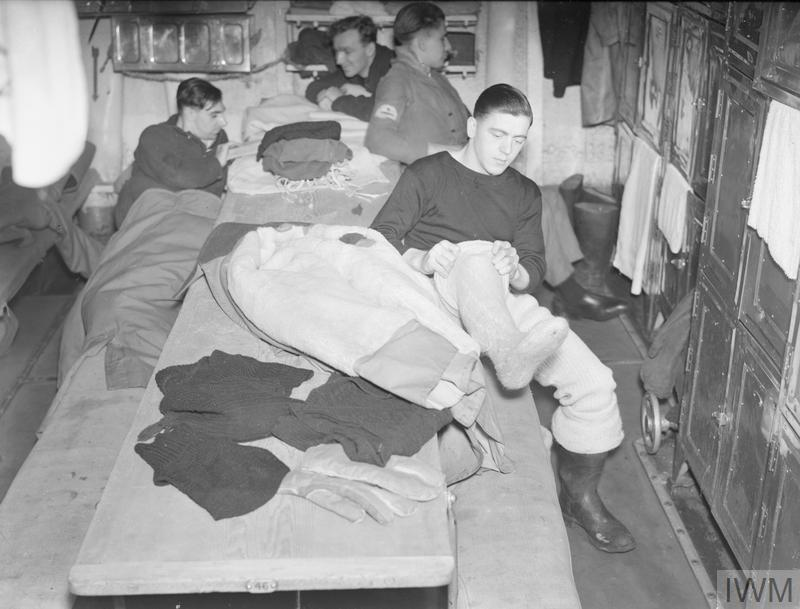 Lookout on board HMS Sheffield; Lookout on board HMS Sheffield in December 1941. He is dressing for the icy conditions, putting on a sheepskin great-coat, sheepskin gloves, two balaclavas, thick woollen underwear, two pairs of seaboot stockings and several pullovers.