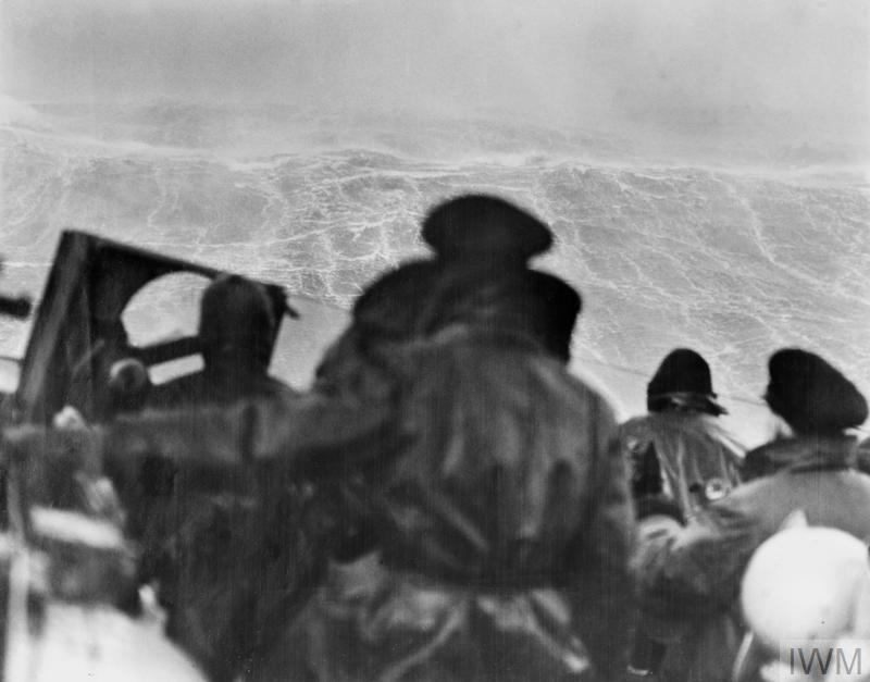 A high wave above HMS Sheffield; A 50-foot (15m) high wave towers above the bridge of the cruiser HMS Sheffield. During this Arctic gale the wind reached speeds of 65 knots (120kph). Visibility was less than 180m. The heavy seas stripped the armoured roof off one of the ship's turrets.