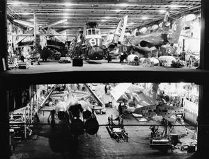 THE WELL-STOCKED HANGARS OF HMS EAGLE. JANUARY 1965, ON BOARD THE AIRCRAFT CARRIER HMS EAGLE.
