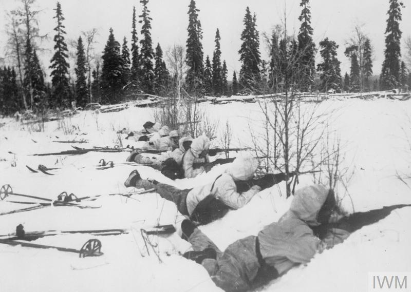 A Finnish ski patrol; A Finnish ski patrol, lying in the snow on the outskirts of a wood in Northern Finland, on the alert for Russian troops, 12 January 1940.