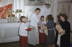 BAPTISING BABIES BORN IN BENOUVILLE MATERNITY HOME IN FRANCE, 27 JULY 1944