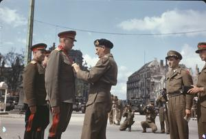 FIELD MARSHAL MONTGOMERY DECORATES RUSSIAN GENERALS AT THE BRANDENBURG GATE IN BERLIN, GERMANY, 12 JULY 1945