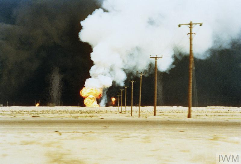 Sabotaged oil wells fill the sky with black smoke as they burn in Kuwait, 1991; Over 600 oil wells were sabotaged by retreating Iraqi forces. Work to put the fires out lasted until November 1991. This photograph was taken by the artist John Keane, who was commissioned as IWM's 'official recorder' in the Gulf War.