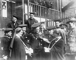 'OUR DAY' SCENE IN LONDON. AMERICAN SAILORS BUYING FLAGS FROM RED CROSS NURSES OUTSIDE THE EAGLE HUT, LONDON