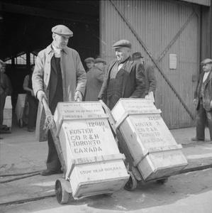 BRITAIN DELIVERS THE GOODS IN WARTIME: DOCK WORKERS IN BRISTOL, ENGLAND, 1940