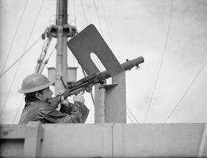 ON BOARD A TROOP TRANSPORT. AUGUST 1941, ON BOARD THE EMPRESS OF AUSTRALIA, ON AN AFRICAN TROOP CONVOY. MOST OF THE TROOPSHIPS EMPLOYED WERE PASSENGER LINERS BEFORE THE WAR. THOUGH A GUN OR TWO MAY HAVE BEEN MOUNTED THE SHIPS STILL HAVE THEIR FACILITIES FOR SPORTS, GAMES AND RECREATION, AND ON THE OCCASIONS WHEN THEY ARE NOT CARRYING LARGE CONTINGENTS OF TROOPS THE SERVICES ARE GLAD TO MAKE USE OF THEM.