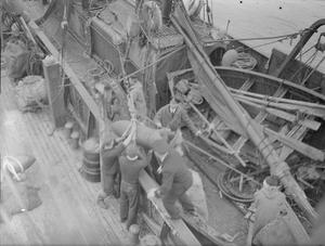 ATTACK ON THE FISHING TRAWLER STRATH BLARE. MARCH 1941. ON THE 8TH OF MARCH 1941, WHEN THE STRATH BLARE WAS OUT OFF THE EAST COAST OF SCOTLAND, SHE WAS ATTACKED BY A HEINKEL BOMBER. THE CREW WERE TAKEN BY SURPRISE WHEN SHE FIRST APPEARED AND CIRCLED ROUND THE TRAWLER. THEY RUSHED TO THE GUNS BUT AS SHE DIVED AGAIN TO MACHINE GUN THE CREW, A WING HIT THE MIZZEN MAST AND SHE CRASHED INTO THE SEA. IN DOING SO PART OF THE HEINKEL'S WING WAS TORN OFF AND ABOUT 6 FEET OF THE MAST WAS TORN AWAY. AS SHE HIT THE MAST TWO BOMBS WERE DROPPED WHICH LANDED ON THE DECK. HERE THE BOMB DISPOSAL SQUAD ARE SHOWN REMOVING THE UNEXPLODED BOMBS FROM THE TRAWLER WHEN SHE RETURNED TO PORT.
