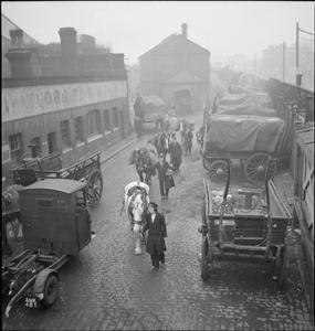VAN GIRL: HORSE AND CART DELIVERIES FOR THE LONDON, MIDLAND AND SCOTTISH RAILWAY, LONDON, ENGLAND, 1943