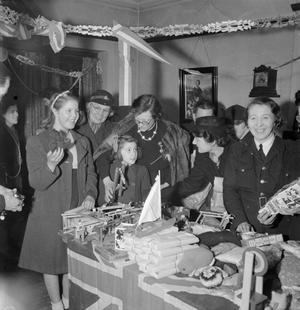 BWRS CHRISTMAS GIFTS DISTRIBUTED TO LONDON'S EAST ENDERS: AMERICAN AID TO THE CANNING TOWN SETTLEMENT, LONDON, ENGLAND, UK, DECEMBER 1944
