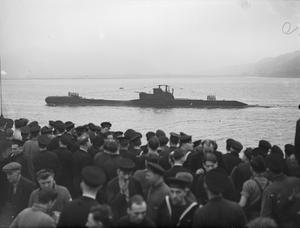 ARRIVAL OF HM SUBMARINE TRIDENT WHICH TORPEDOED THE GERMAN CRUISER PRINCE EUGEN. 19 MARCH 1942, ON BOARD THE DEPOT SHIP HMS FORTH, HOLY LOCH.