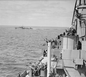 ON BOARD THE SUBMARINE DEPOT SHIP HMS ADAMANT ON CONVOY. 28 MARCH 1942, AT SEA IN THE ATLANTIC. HMS ADAMANT AND ESCORTING WARSHIPS IN ONE OF THE LARGEST CONVOYS OF THE WAR, SAILING FROM THE CLYDE TO FREETOWN CARRYING SUPPLIES AND PERSONNEL FOR THE FORCES IN THE MIDDLE EAST. IT WAS HMS ADAMANT'S MAIDEN VOYAGE.