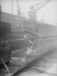 HMS KING GEORGE V AFTER COLLISION WITH HMS PUNJABI. 17 MAY 1942, GLADSTONE DOCK, LIVERPOOL. HMS KING GEORGE V IN THE DOCK FOR REPAIRS AFTER RETURNING TO THE UNITED KINGDOM FROM ICELAND FOLLOWING HER COLLISION WITH HMS PUNJABI ON 1 MAY 1942. PUNJABI WAS SLICED IN TWO AND LOST.