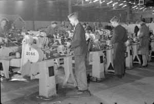 BOYS TRAIN ON LATHES AT A ROYAL ORDNANCE FACTORY, UK, c 1942