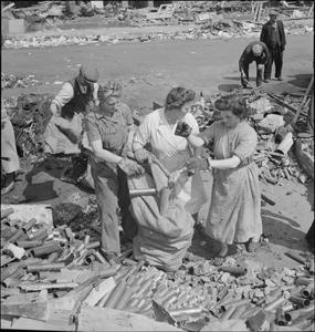 SALVAGING MATERIAL FROM THE WRECKAGE OF A BOMB DAMAGED FACTORY, c 1944