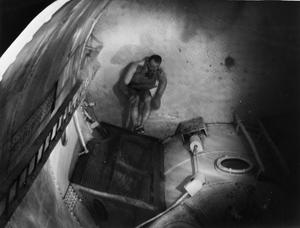 DAVIS APPARATUS BRINGS SUBMARINE-TRAPPED MEN TO SAFETY. 14 DECEMBER 1942, HMS DOLPHIN, AT GOSPORT, THE WAY TO SAFETY FOR BRITAIN'S UNDERWATER FIGHTERS SHOULD THEY BE TRAPPED IN A DOOMED SUBMARINE LIES THROUGH THE ESCAPE HATCH AND DAVIS SUBMERGED ESCAPE APPARATUS. WITH A RUBBER BAG FILLED FROM A SMALL CYLINDER OF COMPRESSED OXYGEN STRAPPED TO HIS CHEST, NOSTRILS CLOSED BY RUBBER CLIPS, EYES PROTECTED BY SPECIAL GOGGLES, THE SUBMARINE SAILOR CAN RISE SLOWLY TO THE SURFACE. HE BREATHES OUT THROUGH A CONTAINER OF CHEMICAL ABSORBENT WHICH PURIFIES THE AIR SO THAT IT CAN BE RE-INHALED. TRAINEES FOR BRITAIN'S SUBMARINE SERVICE LEARNING TO USE THE DAVIS APPARATUS INSIDE A GIANT TANK.
