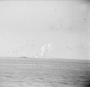 INDOMITABLE FOUGHT THROUGH - MALTA CONVOY. AUGUST 1942, ABOARD HMS VICTORIOUS. THE AIRCRAFT CARRIER HMS INDOMITABLE SAILING THROUGH A HAIL OF BOMBS (AS SEEN FROM THE VICTORIOUS) DURING THE GREAT SEA-AIR BATTLE WHICH COVERED THE PASSAGE OF A VITAL MALTA CONVOY IN AUGUST 1942. THE INDOMITABLE WAS DAMAGED BY NEAR MISSES.