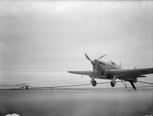 THE FLEET AIR ARM ON BOARD THE BRITISH CARRIER HMS ARGUS. 15, 16, AND 17 AUGUST 1943, ON BOARD HMS ARGUS OFF LAMLASH. CELEBRATING HER SILVER JUBILEE, 25 YEARS CONTINUOUS SERVICE, THE ARGUS IS NOW BEING USED TO TRAIN FLEET AIR ARM PILOTS ON THE ART OF LANDING ON A CARRIER AT SEA.