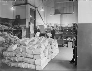 IN A ROYAL NAVAL WAR LIBRARY. 27 APRIL 1944, ROYAL NAVAL WAR LIBRARY, LIVER BUILDING, LIVERPOOL. THOUGH IT IS CHIEFLY FOR THE USE OF SHORE BASED PERSONNEL, SMALL BAGS EACH CONTAINING 20 BOOKS ARE MADE UP FOR ISSUE TO SHIPS WHEN THEY COME INTO PORT.