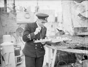 CHIEF ENGINEER AND MODELLER SERVED UNDER TWELVE ADMIRALS. 23 MARCH 1944, HARWICH. WARRANT MECHANICIAN JOHN JOHNS, RN, OF LOOE, CORNWALL, CHIEF ENGINEER OF HMS KITTIWAKE, JOINED THE NAVY 25 YEARS AGO, DURING THIS TIME HE HAS SERVED UNDER 12 ADMIRALS IN DIFFERENT SHIPS.