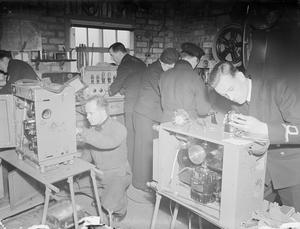 DOCKYARD CINEMA MAINTENANCE UNIT. 20 JANUARY 1944, ROSYTH. IT IS THE JOB OF THE ROYAL NAVY CINEMA MAINTENANCE UNIT TO KEEP CINEMA EQUIPMENT FOR THE FLEET IN WORKING ORDER.