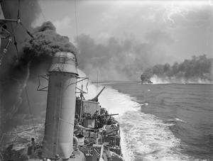 BRITISH CRUISER BOMBS SHORE TARGETS IN THE GAETA AREA. 18 MAY 1944, ON BOARD THE AMERICAN DESTROYER USS MACKENZIE, IN THE MEDITERRANEAN OFF THE ITALIAN COAST NEAR GAETA. DURING THE SUCCESSFUL BOMBARDMENT OF ENEMY BATTERIES, DUMPS, AND ROADS TO THE WEST OF GAETA CARRIED OUT BY THE CRUISER HMS DIDO IN SUPPORT OF THE ARMY.