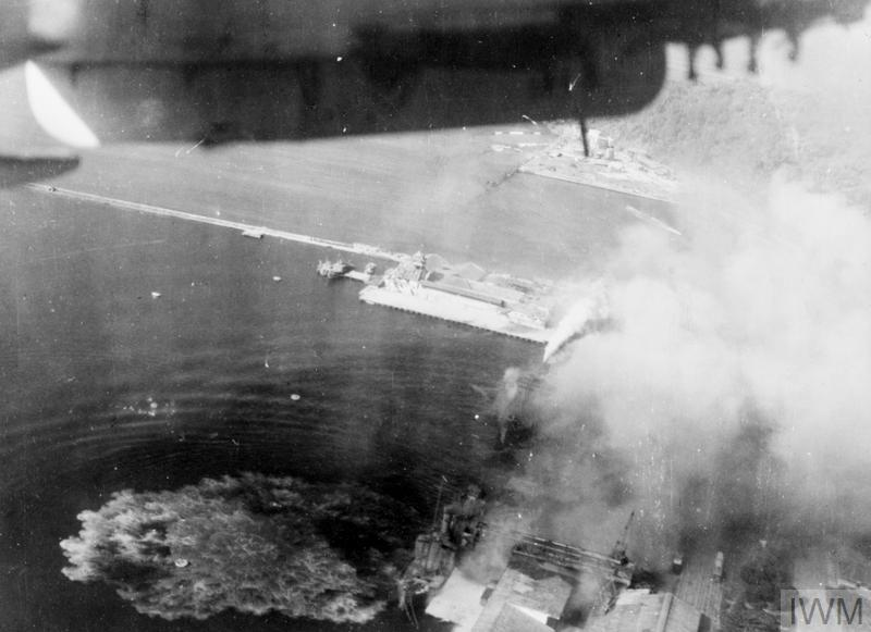AIR ATTACKS ON JAPANESE SHIPPING SCORES MANY DIRECT HITS. FROM ONE OF THE ATTACKING PLANES DURING THE EASTERN FLEET'S CARRIER-BORNE AIRCRAFT ATTACK ON PADANG, ON THE WEST COAST OF SUMATRA, 24 AUGUST 1944.
