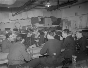 LISTENING-IN AT SEA. 27 JANUARY 1945, ON BOARD HMS LOCH INSH WHEN MEN OFF WATCH WERE LISTENING-IN TO THE NEWS WHILE ENJOYING A GAME OF CARDS ON THE MESS DECK. THE RADIO IS RELAYED THROUGHOUT THE SHIP BY LOUD SPEAKERS FROM A MASTER SET.
