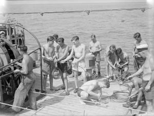MAKING THE SEAS SAFE AGAIN. AUGUST 1945, AT SEA IN THE GULF OF GENOA. WITH THE 12TH MINESWEEPING FLOTILLA, OPERATING IN THE GULF OF GENOA UNDER THE COMMAND OF COMMANDER C SIMPSON, DSC, RN, COMMANDER MINESWEEPING WESTERN ITALY. THEY WORK FROM SURRENDERED ENEMY CHARTS AND ARE AIDED BY SUPERMARINE WALRUS AIRCRAFT AND THE US NAVY BLIMP MINE-SPOTTING DETACHMENT.
