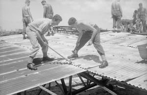 ROYAL NAVY HELPS IN MAURITIUS REHABILITATION WORK. MARCH 1960, PORT LOUIS, CAPITAL OF MAURITIUS. THE CRUISER HMS GAMBIA HELPING IN REHABILITATION WORK FOLLOWING TWO DISASTROUS CYCLONES WHICH STRUCK THE BRITISH ISLAND OF MAURITIUS IN THE INDIAN OCEAN.