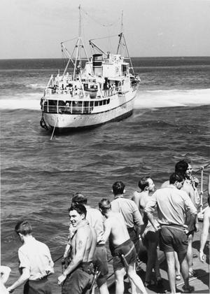 NAVY'S DRAMATIC REEF RESCUE IN FIJI ISLANDS. OCTOBER 1968, ON BOARD THE DESTROYER HMS FIFE, OFF TOTOYA, IN THE FIJI ISLANDS. 42 PASSENGERS INCLUDING WOMEN AND CHILDREN AND A CREW OF 37 WERE WINCHED BY HELICOPTER TO THE GUIDED MISSILE DESTROYER HMS FIFE FROM THE MV TUILAU, A FIJIAN INTER-ISLAND TRADING SHIP. THE VESSEL, WITH A CARGO OF COPRA WENT AGROUND ON A REEF. A HELICOPTER FROM HMS FIFE PILOTED BY LIEUT CDR G STOCK TRANSFERRED HER EXECUTIVE OFFICER CDR J BENSON, AND SHIPWRIGHT OFFICER, SUB LIEUT B HARDISTY, AND R/O T HODGKINSON TO THE STRICKEN SHIP. LIEUT N TRUTER CARRIED ALL THE CHILDREN BY WINCH TO THE SAFETY OF HMS FIFE. HMS PUMA JOINED IN UNSUCCESSFUL ATTEMPTS TO REFLOAT THE STRICKEN SHIP.