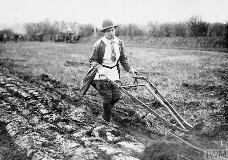 A member of the Women's Land Army operating a single-furrow plough on a British farm.