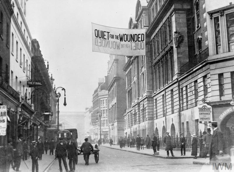 A large sign requesting 'Quiet for the Wounded' hangs outside Charing Cross Hospital at Agar Street, London, September 1914. Heavy traffic has been diverted to minimise noise in the street.