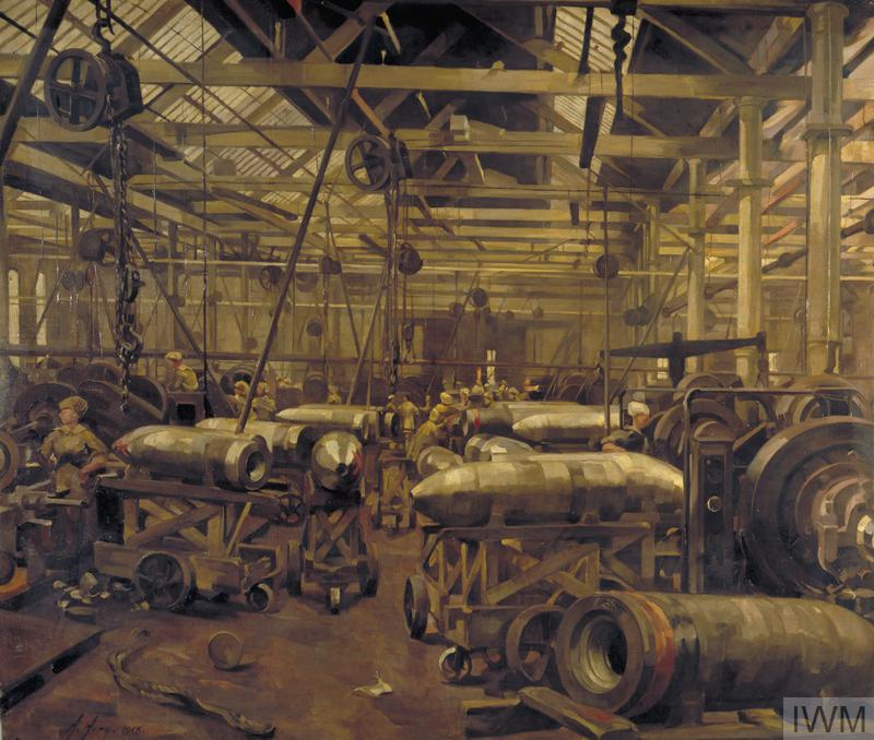 The interior view of a munitions factory showing the production of 15 inch shells by women factory workers. There are winches hanging from the ceiling and large steel shell cases sitting on wooden trolleys in the centre of the image.