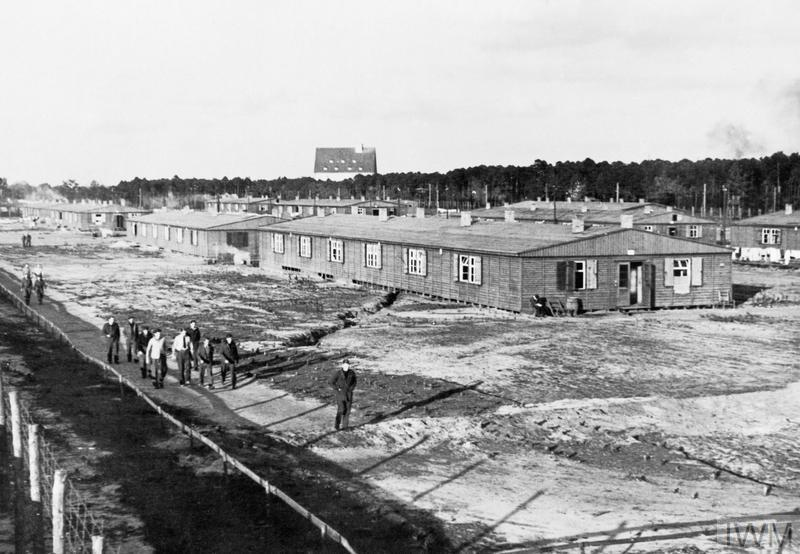 Prisoners having a walk around compound of Stalag Luft III, Sagan. Note the accommodation barracks in the background.