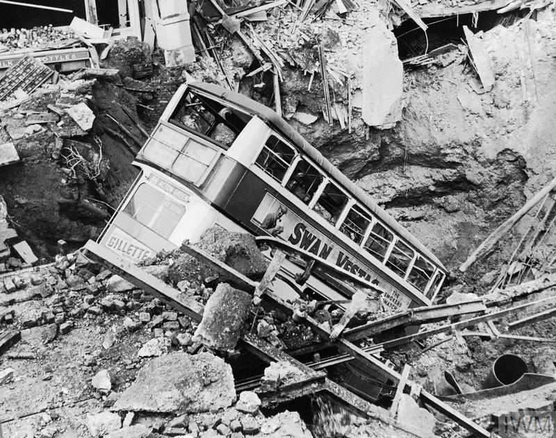 A bus lies in a crater in Balham, south London, after a bombing raid.