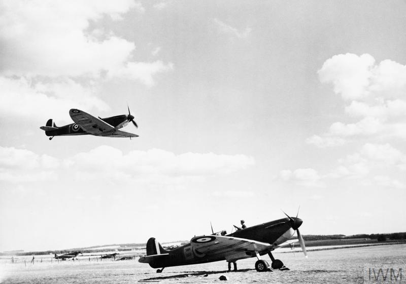 A Spitfire Mk I of No. 19 Squadron flies over another parked aircraft at Fowlmere, September 1940.