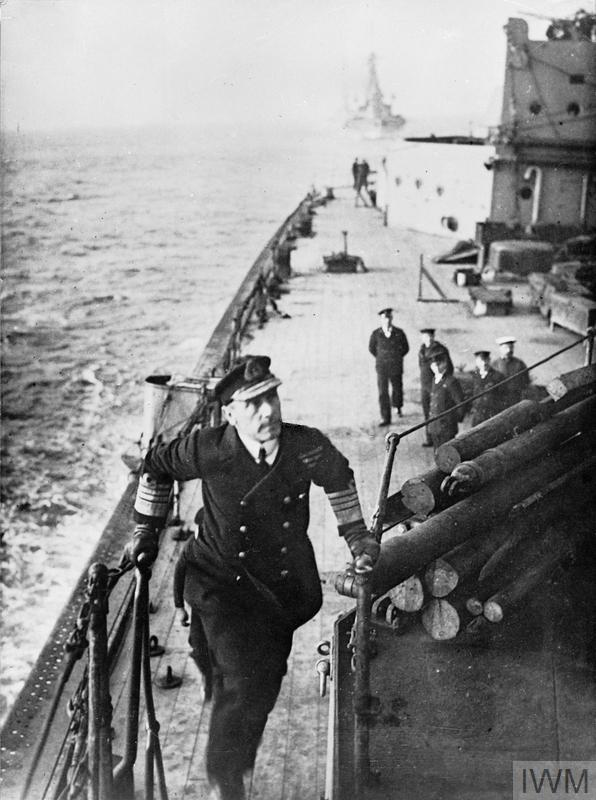 Admiral Sir John Jellicoe, Commander in Chief of the Grand Fleet, reaching the top of a flight of steps on board a battleship. A small group of sailors is stood below looking up at him whilst a capital ship sails astern of the ship.