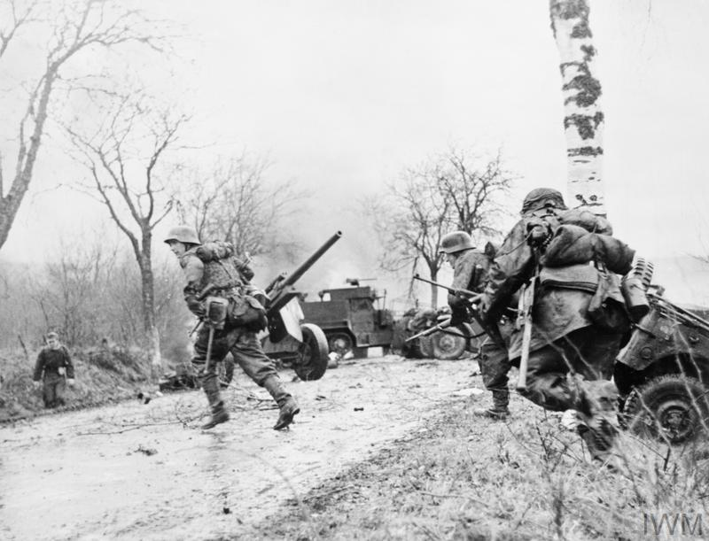 German SS troops double across a road in a staged photo after the destruction of an American convoy of jeeps and half-tracks in the Ardennes, 16 December 1944.