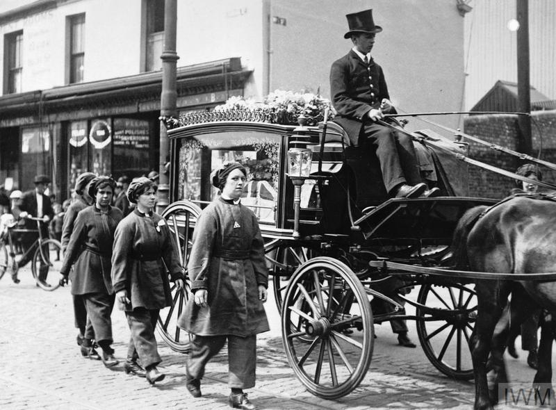 Female munitions workers walk beside the horsedrawn hearse of one of their colleagues who had been killed at work, August Bank Holiday 1917. They are wearing their factory uniforms as a sign of respect during the funeral procession through Swansea.