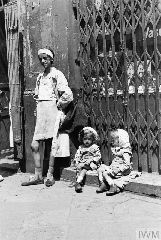An emaciated mother with her twin daughters in the ghetto, summer 1941.