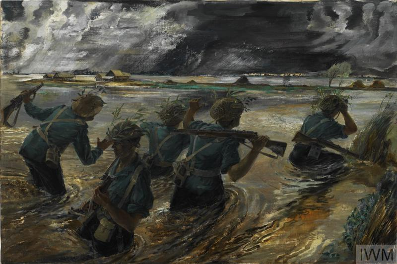 Five soldiers wading through a flooded paddy field