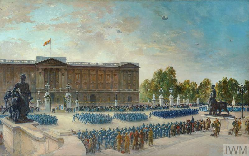 A Royal Air Force anniversary parade taking place directly outside Buckingham Palace. Columns of RAF personnel in blue uniform march from left to right. They are watched by fellow RAF personnel and British soldiers in the foreground and by a mixture of civilians and military personnel standing in front of the palace gates.