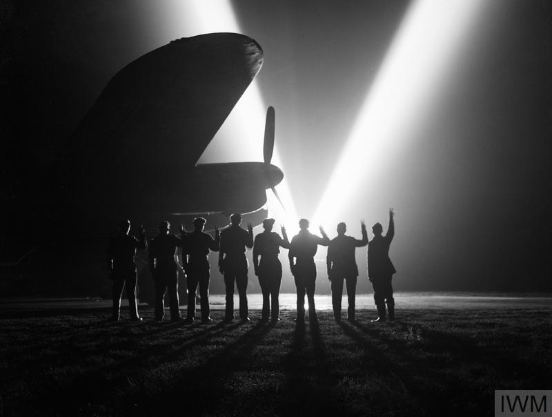 Ground crew on a RAF Bomber Command station in Britain return the V-sign to a neighbouring searchlight crew . Silhouetted is the nose of a Lancaster.