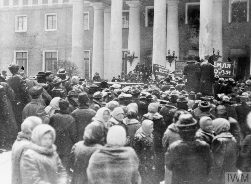 "A crowd gathered outside the Duma; some carry banners bearing the slogan ""Land and Freedom""."