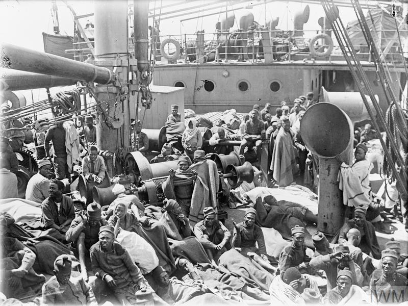 """German East African Campaign. Men of the 3rd Nigerian Battalion felt the cold when nearing Cape Town. On board the Transport """"MENDI"""" between Calabar and Cape Town, November 1916."""