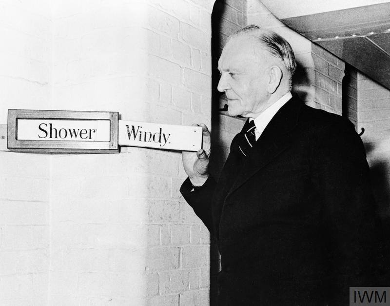 George Rance, the Clerk and Custodian of the Cabinet War Rooms, adjusting the weather indicator boards in the main corridor of the Cabinet War Rooms. When a heavy raid was in progress above, Rance, as a private joke, would put up the board bearing the word 'Windy'.