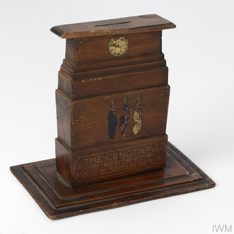 wooden model of the Cenotaph (H 15cm x W 17cm x D 10cm) with slot for money at its top and bearing details in coloured transfers: a clock face (showing the hands at eleven o'clock); three flags -Blue Ensign, Union Jack and White Ensign) and the inscription in three lines: 'THE CENOTAPH / IN MEMORY OF / OUR GLORIOUS DEAD'.