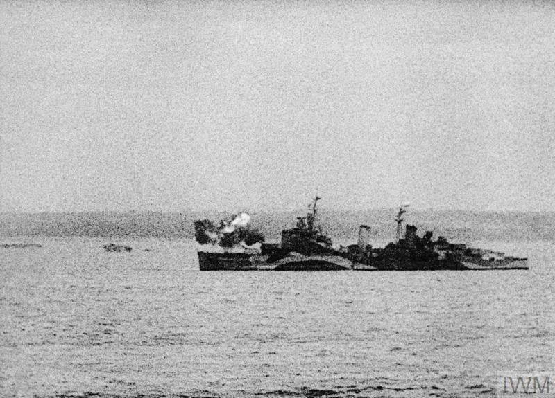 HMS BELFAST at anchor off the Normandy beachhead, firing A and B turrets.